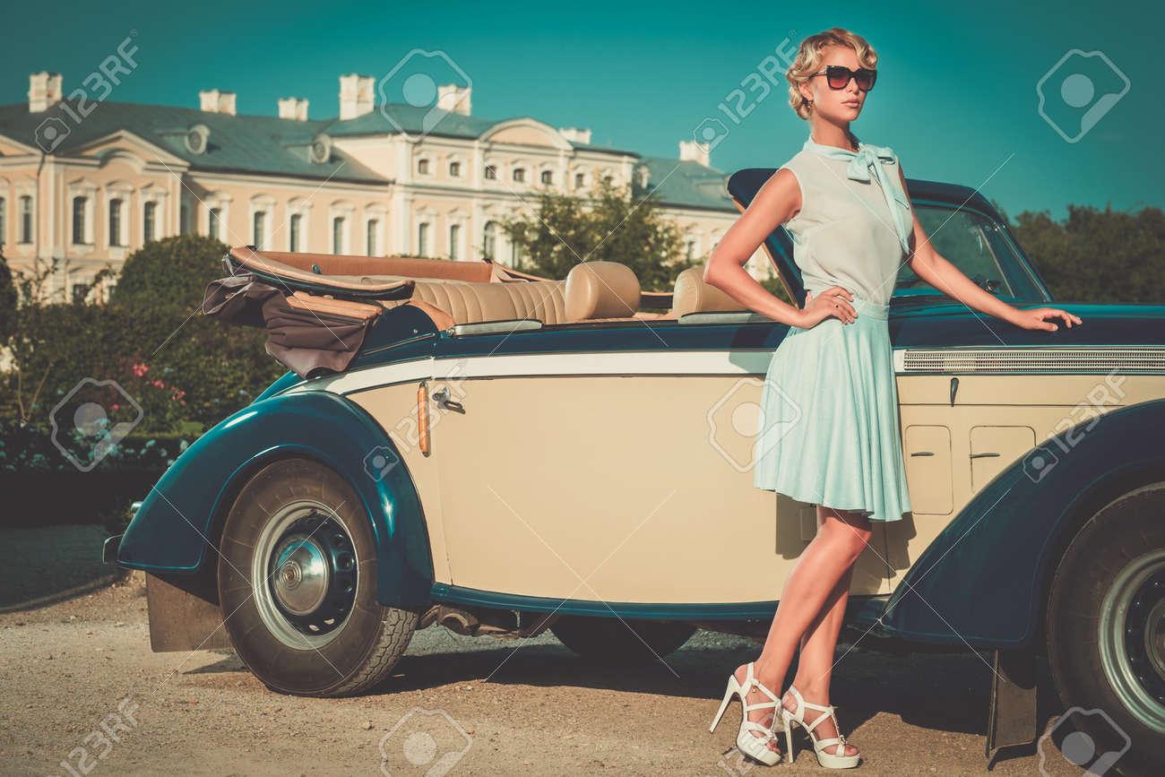 Beautiful lady near classic convertible Stock Photo - 57721200