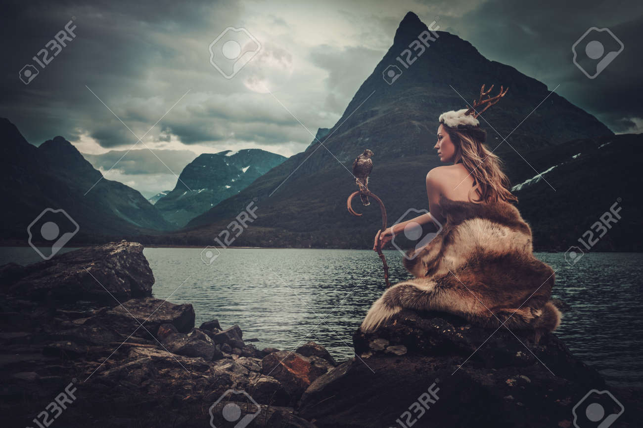 Nordic goddess in ritual garment with hawk near wild mountain lake in Innerdalen valley, Norway. - 60870755