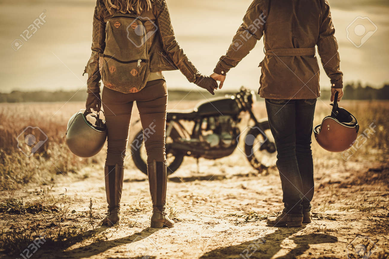 Young, stylish cafe racer couple on the vintage custom motorcycles in a field. Stock Photo - 63375081