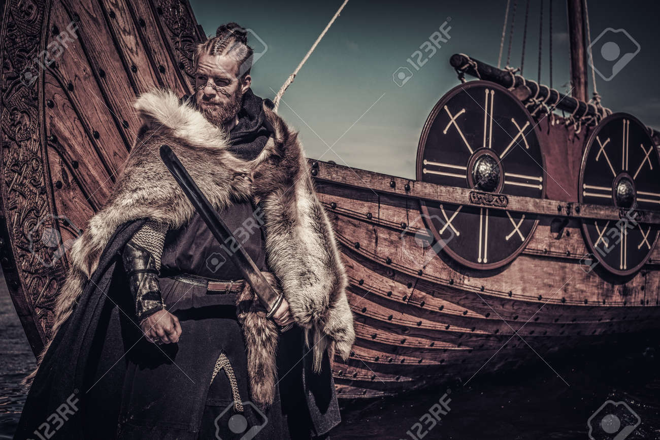 Viking warrior with sword standing near Drakkar on seashore. - 66159214