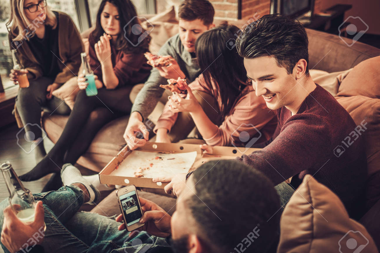Group of multi ethnic young friends eating pizza in home interior Stock Photo - 68523403