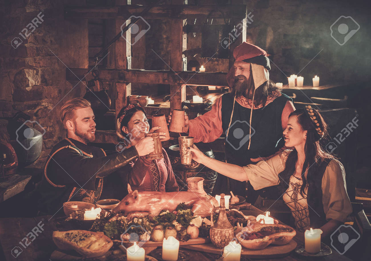 Medieval people eat and drink in ancient castle tavern. - 94536888
