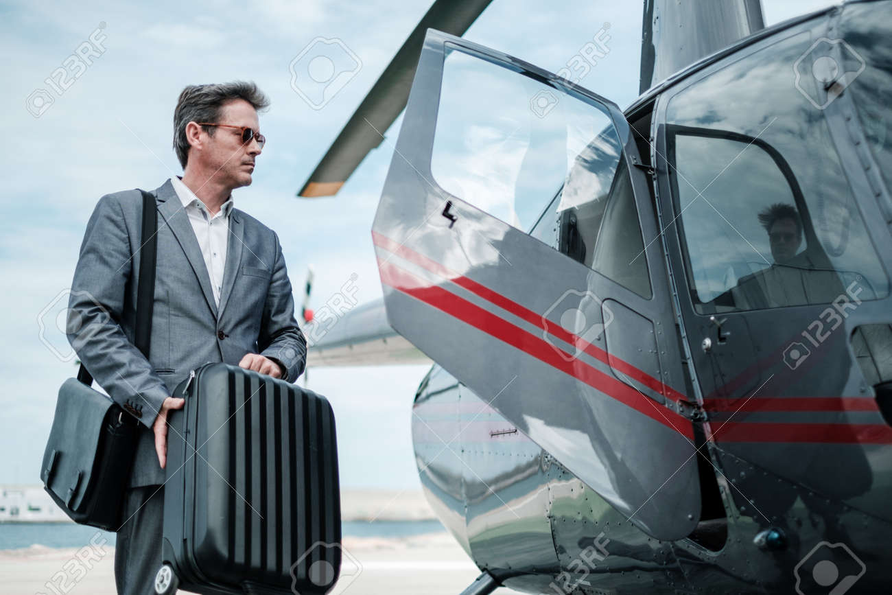 Businessman near private helicopter - 103588174