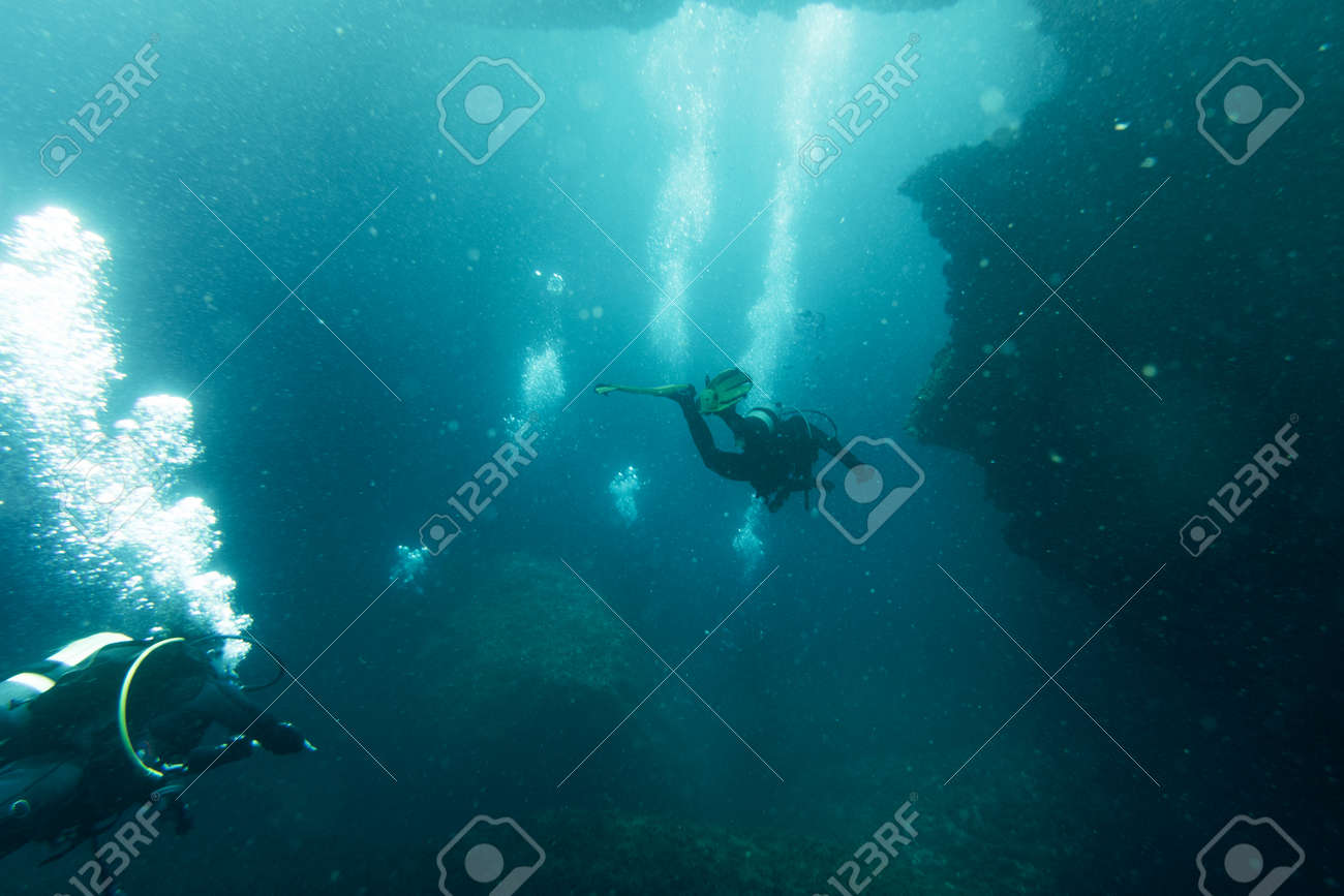 Scuba divers swimming under water - 126571283