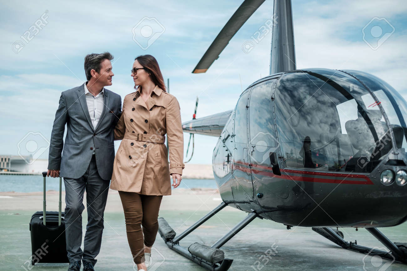 Young business couple near private helicopter - 127253031