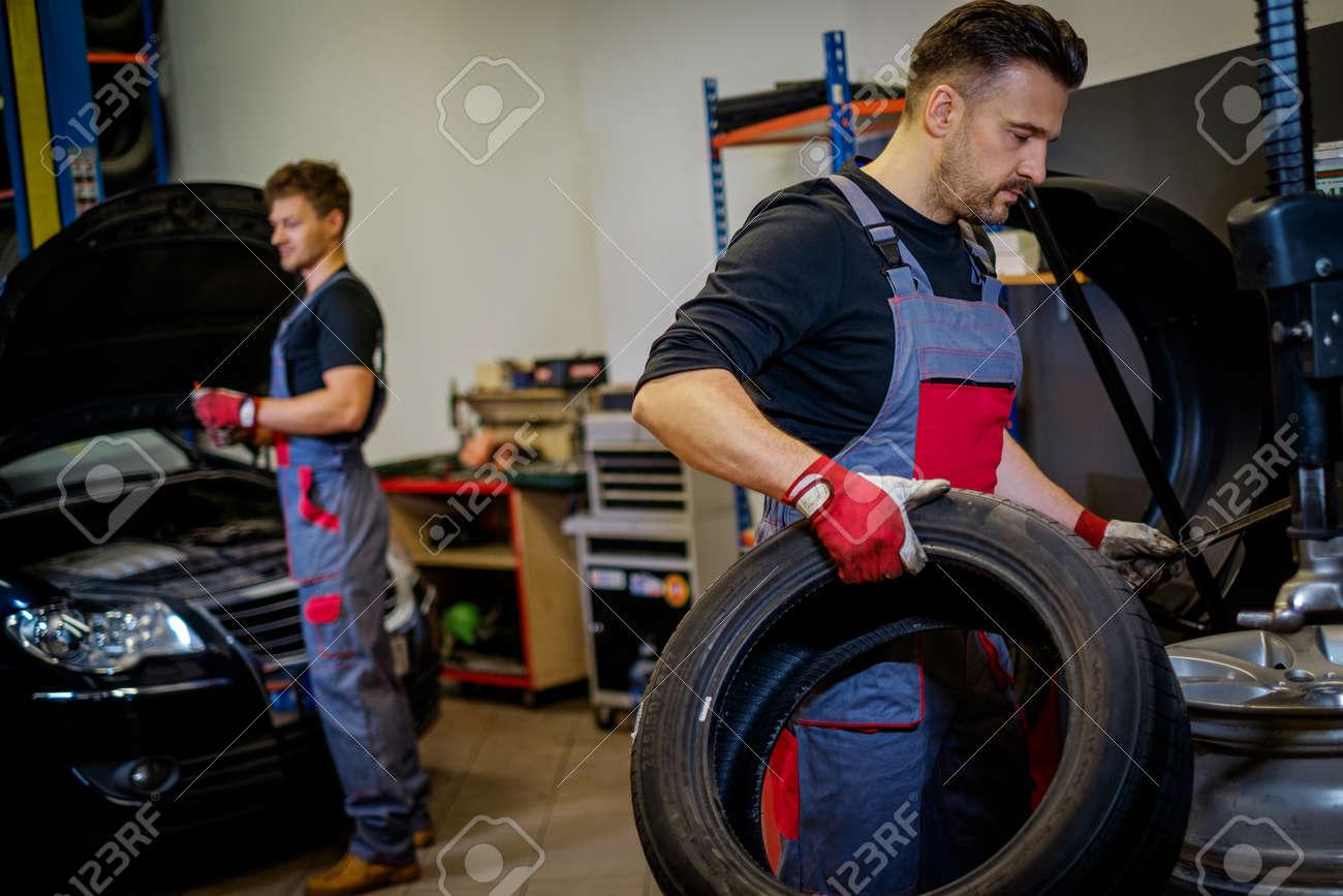 Car mechanic mounts tire on wheel in a workshop - 130381157