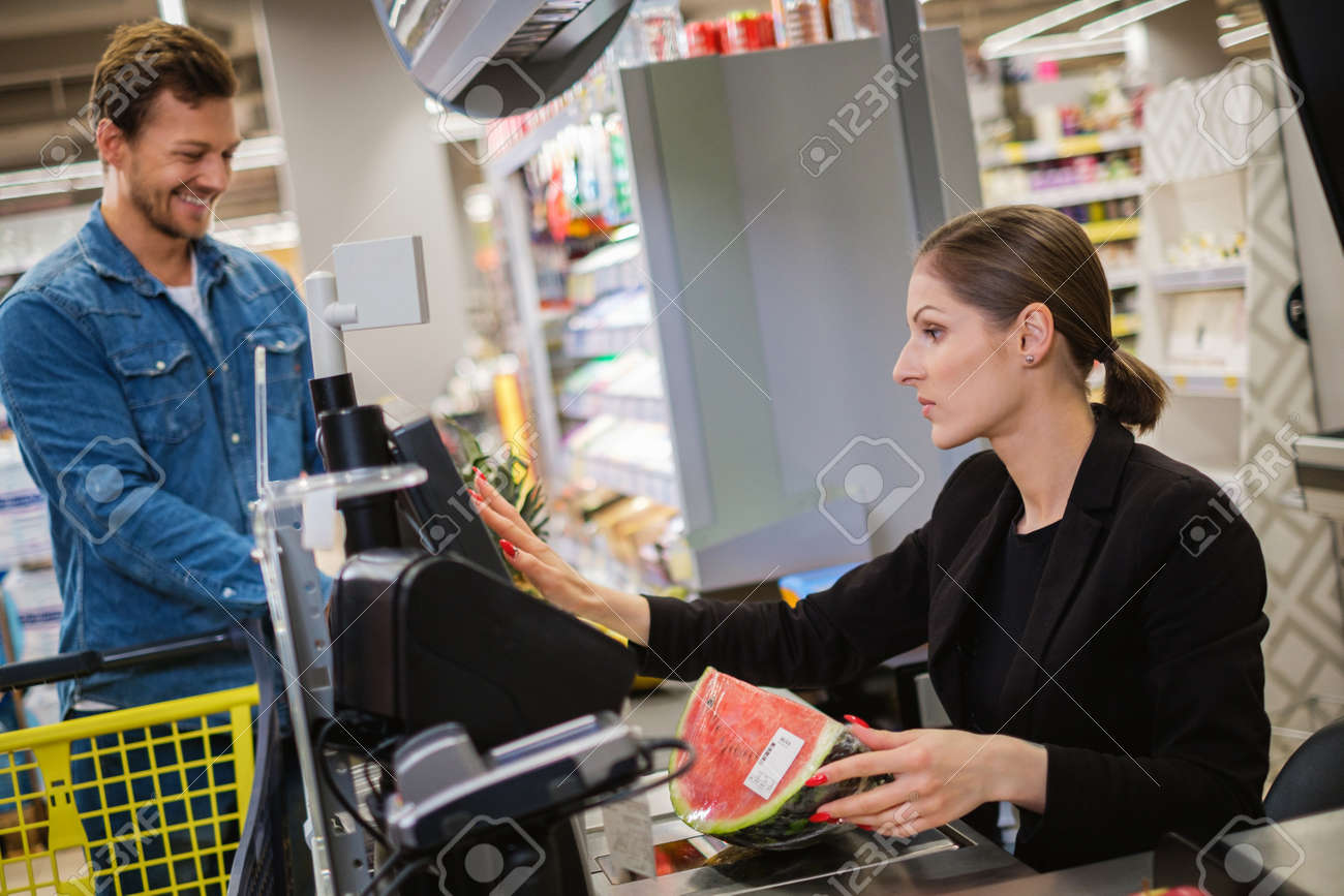 Man buying goods in a grocery store - 131011446