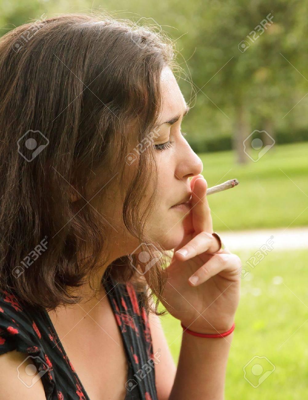 jeune femme fumant une cigarette roulée, côté portrait Banque d'images - 14191577