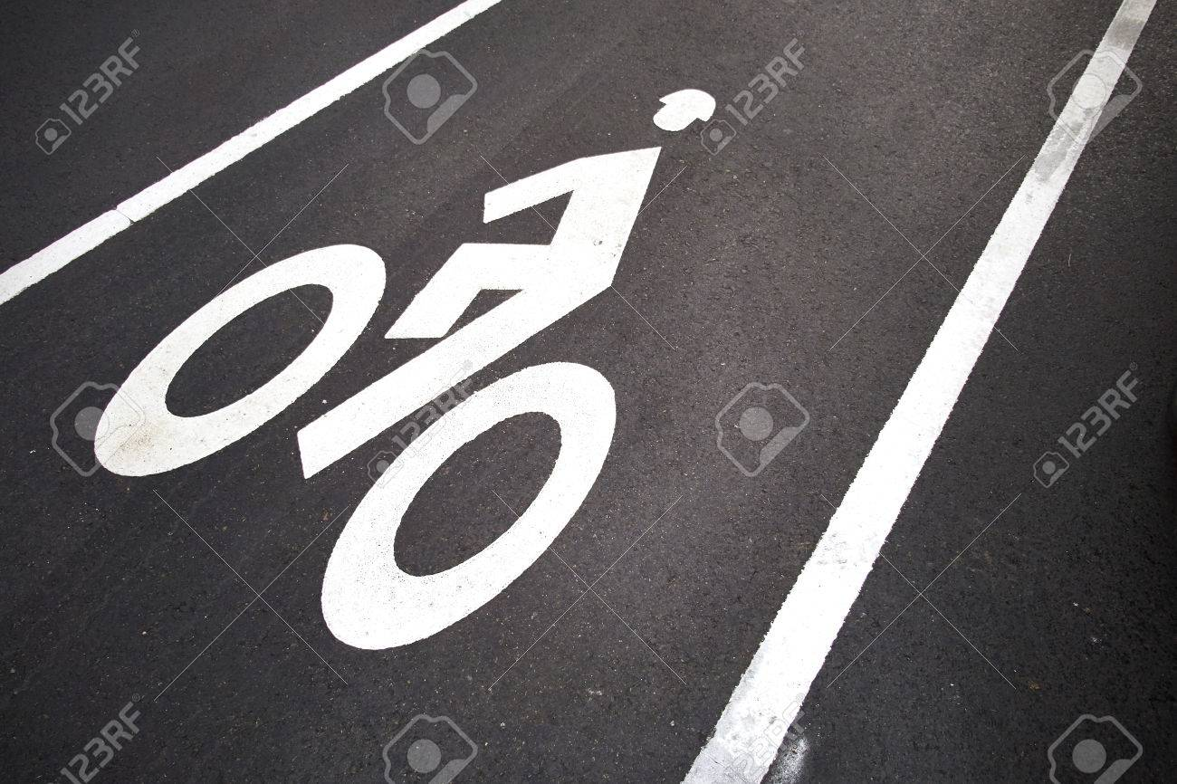 Bicycle lane. White mark of bicycle and white arrow pointing one way on asphalt path - 24858453