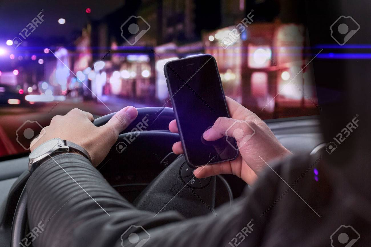 young man holding a smartphone while driving. dangerous travel situation with distraction from street - 47693968