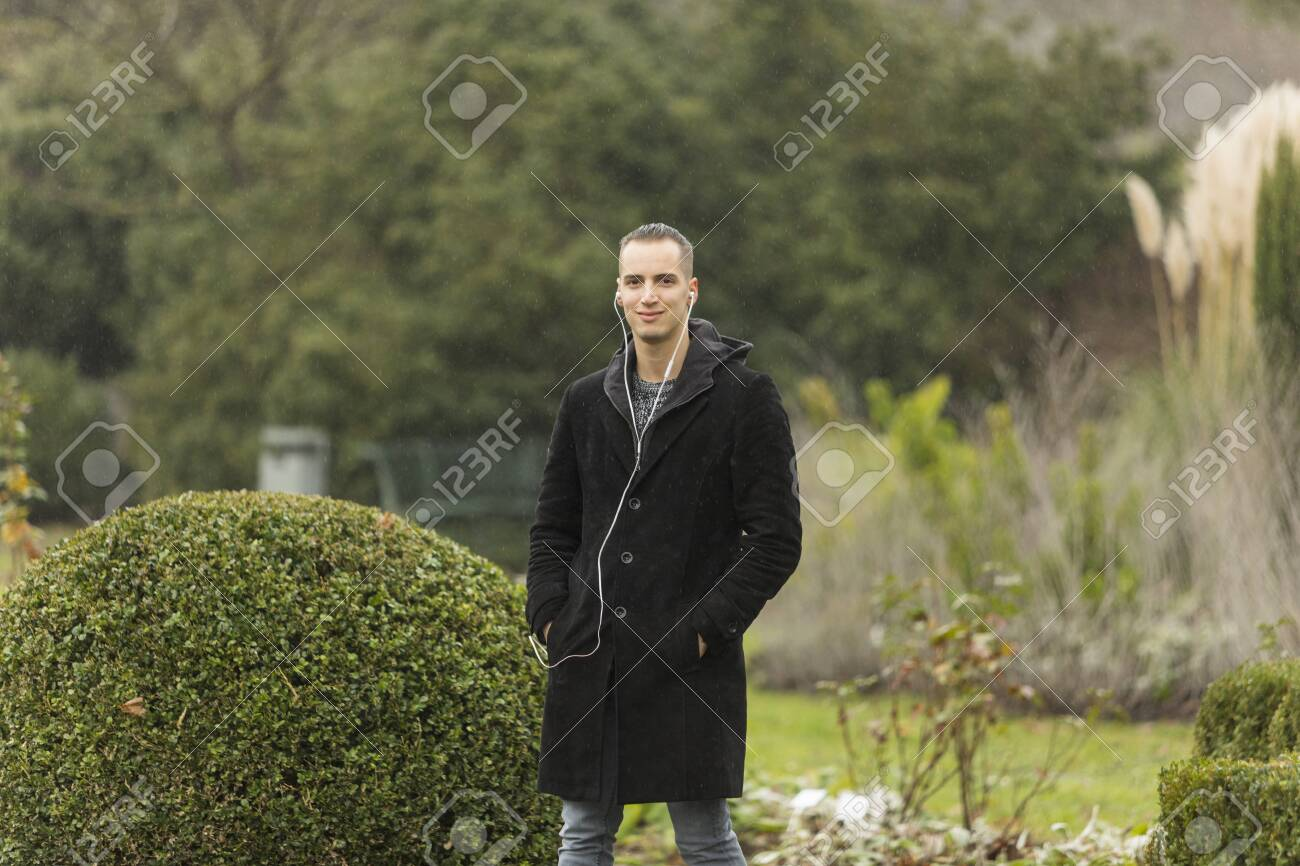 Young Man Listening To Earphones Posing In Topiary Garden Stock Photo Picture And Royalty Free Image Image 143965858