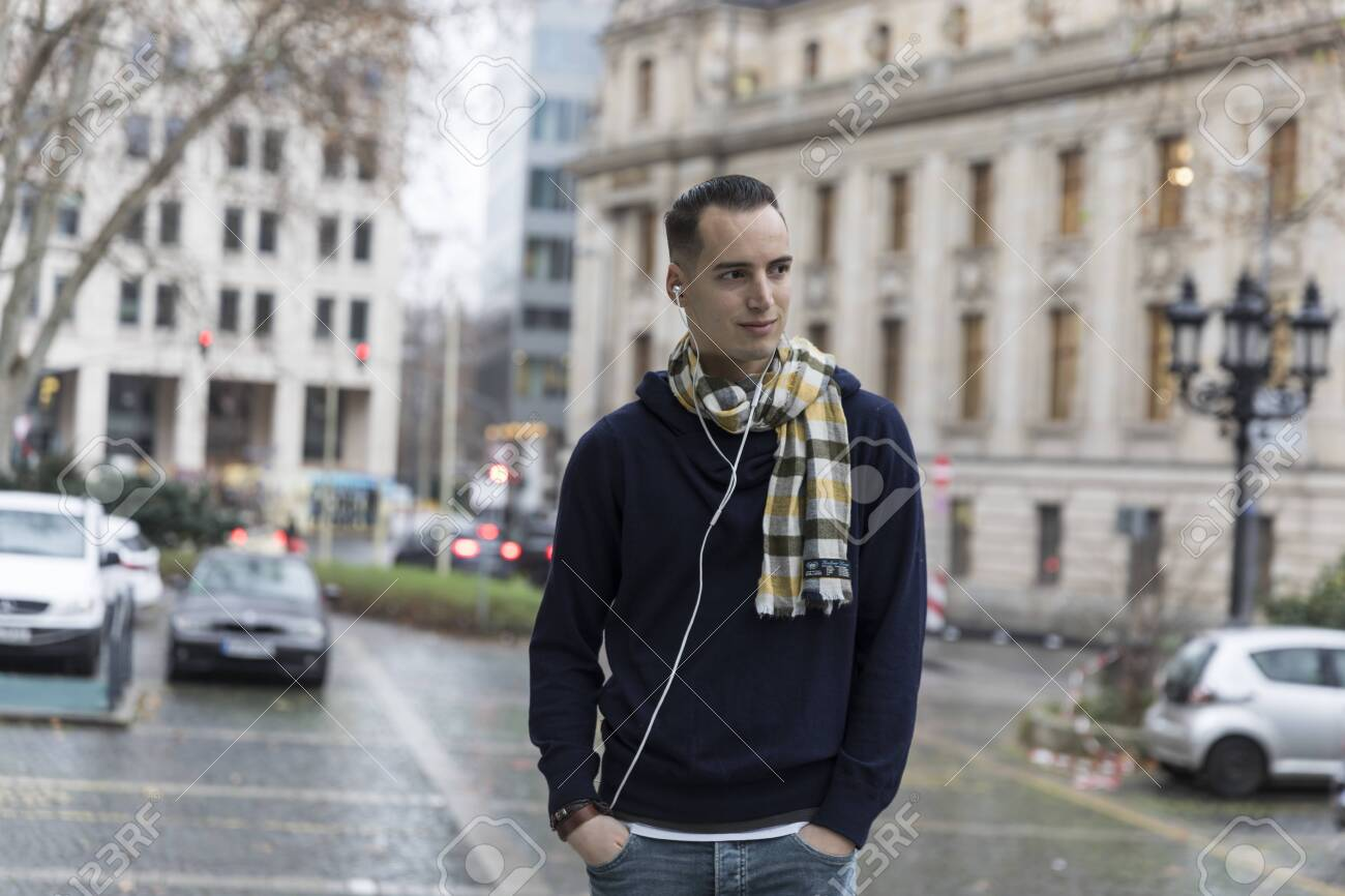 Young Man with Earphones and Head Turned in Urban Setting - 144008625