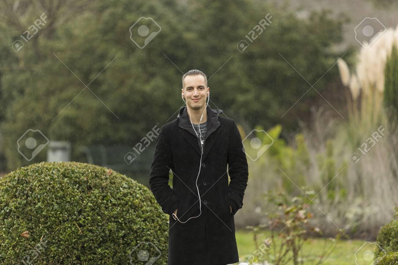 Young Man Wearing Coat and Listening to Earphones Posing in Garden - 143965966