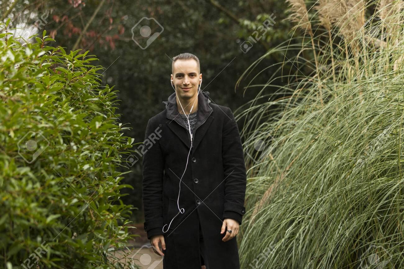 Young Man with Earphones and Coat Standing in Botanical Garden - 143965958