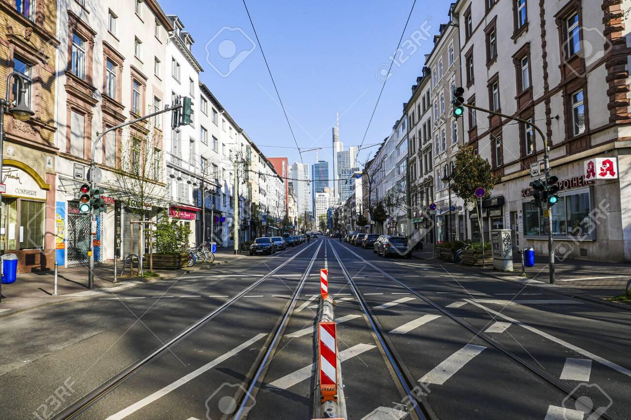 Coronavirus lockdown. Frankfurt, Germany. April 5, 2020. Empty street at Schweizer Platz during quarantine with financial district skyscrapers in vanishing point. - 144821553