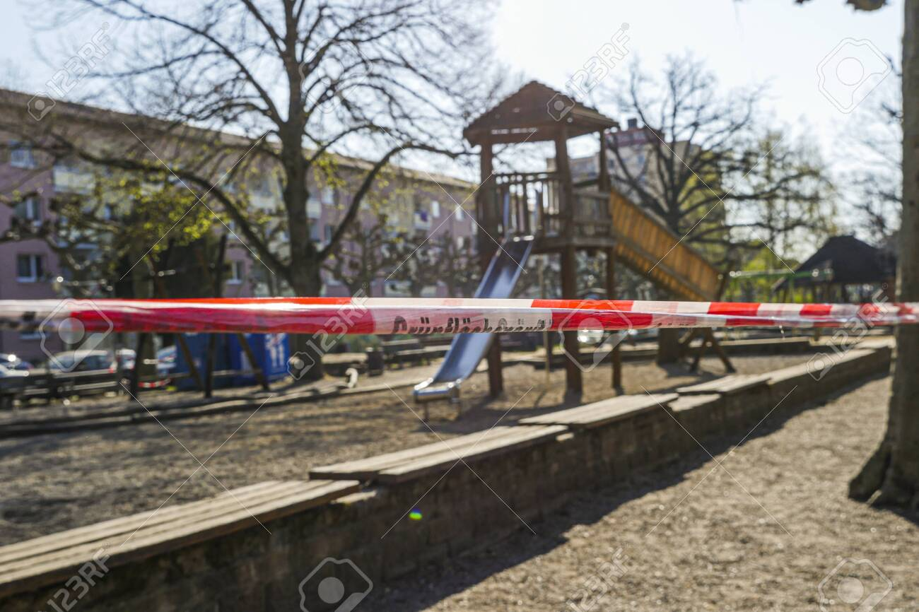 Children's playground with barricade tape preventing access during covid-19 quarantine. Focus on foreground. - 145067119