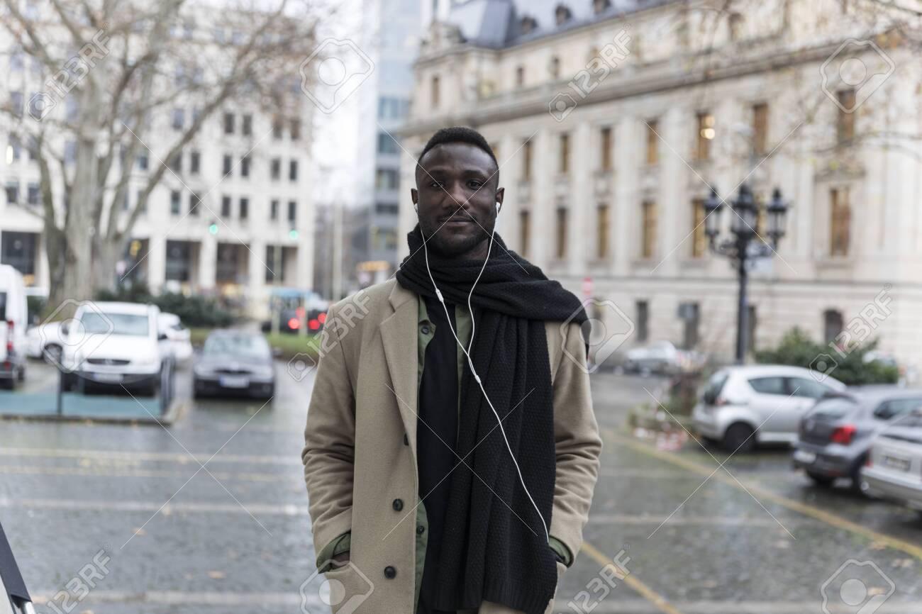 Young Black Man Wearing Beige Coat Posing in City - 146783184