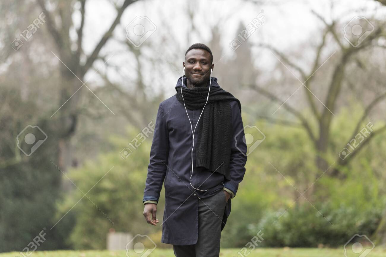 Young Man Walking in Park with Hand in Pocket - 146783200