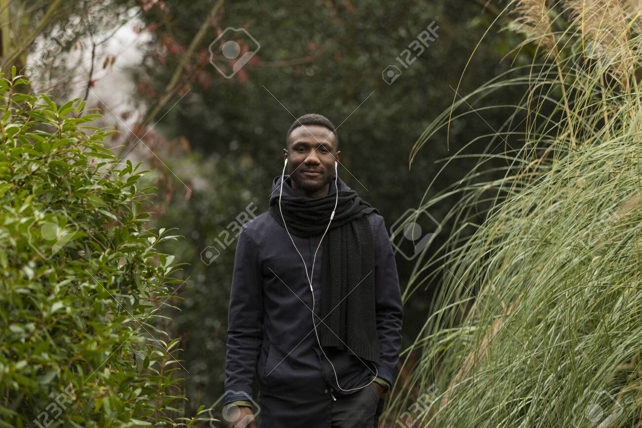 Young Man with Earphones Posing in Park - 146783204
