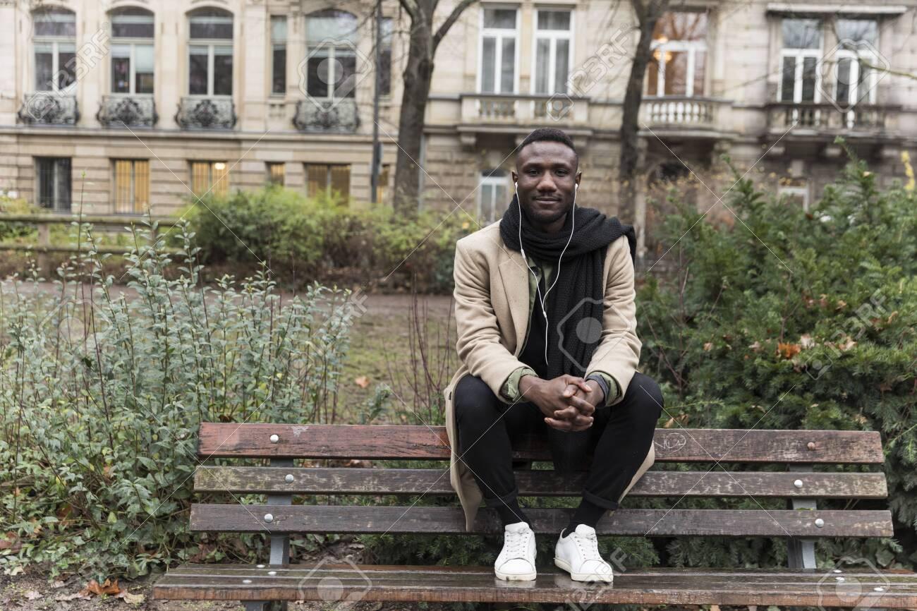 Young Black Man Sitting on Public Park Bench Backrest - 146783222