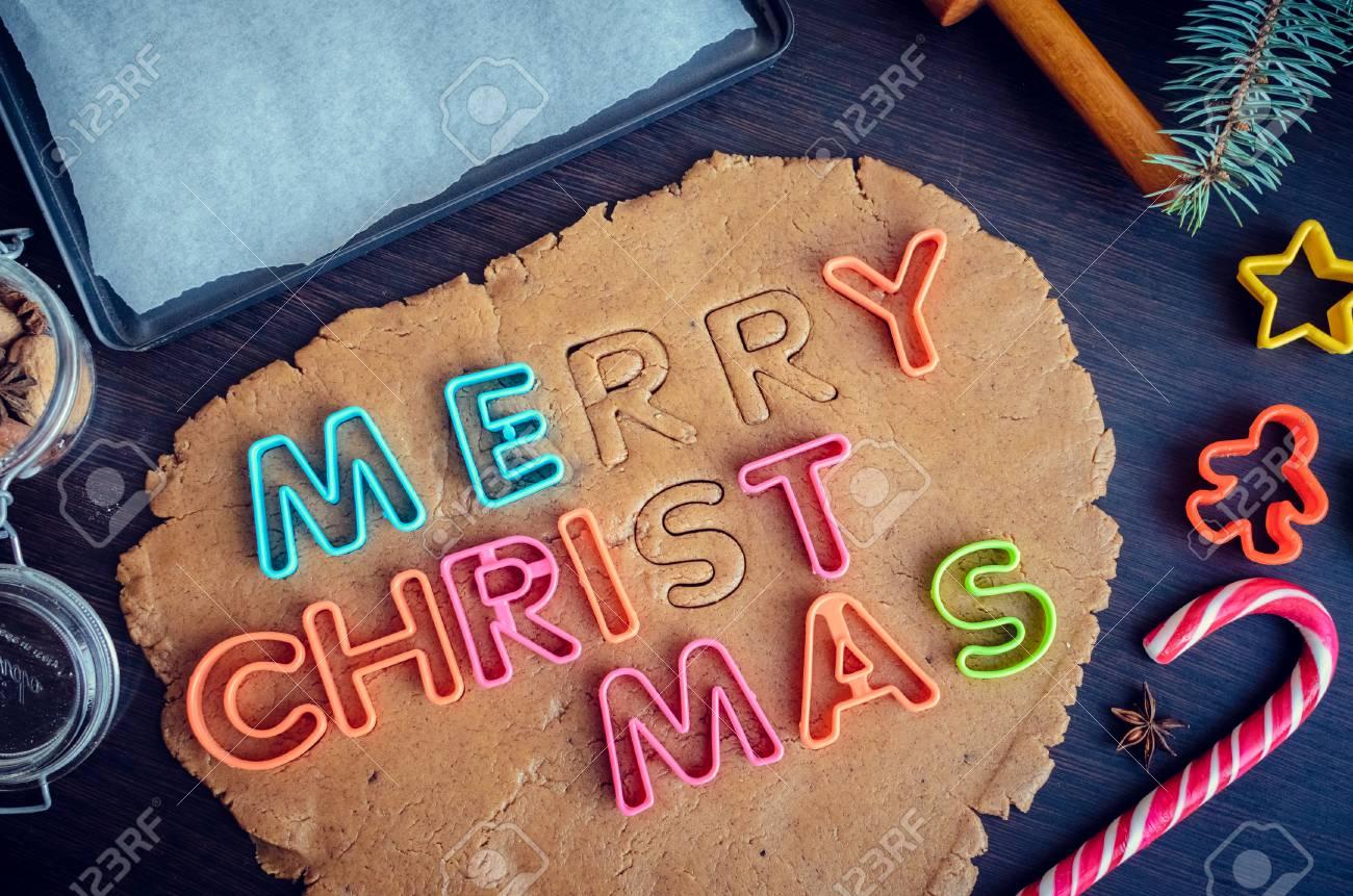 Letras De Cortadores Em Uma Massa Frase Feliz Natal Etapa De Fazer Cookies Tradicionais Do Pão De Espécie Do Natal Massa E Cortadores Crus Para Os