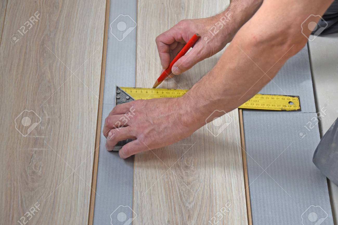 Hands Of A Carpenter Measuring Wood Laminate Flooring Stock Photo 43155102