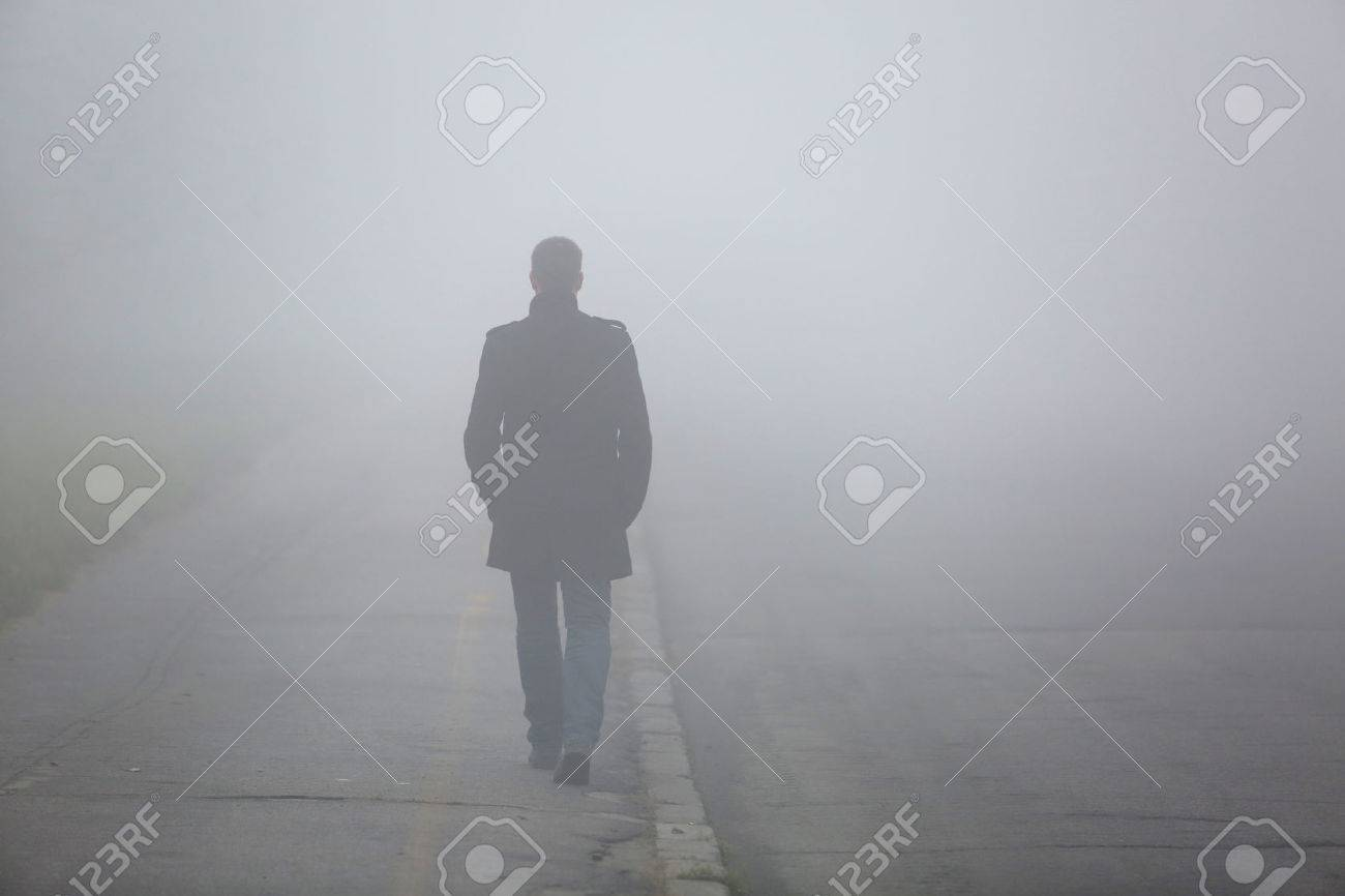Alone Man from back walking through the fog on street - 52651500