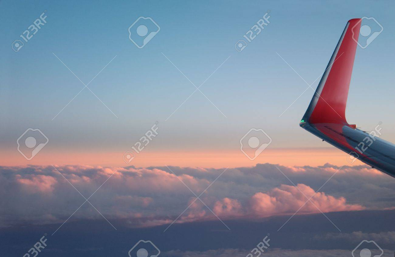 Airplane wing and clouds below, lit orange by the setting sun. Stock Photo - 3257656