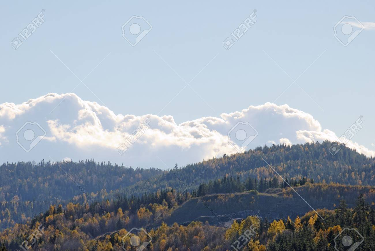 Billowing clouds over mountains clad in autumn-coloured forests Stock Photo - 3571304