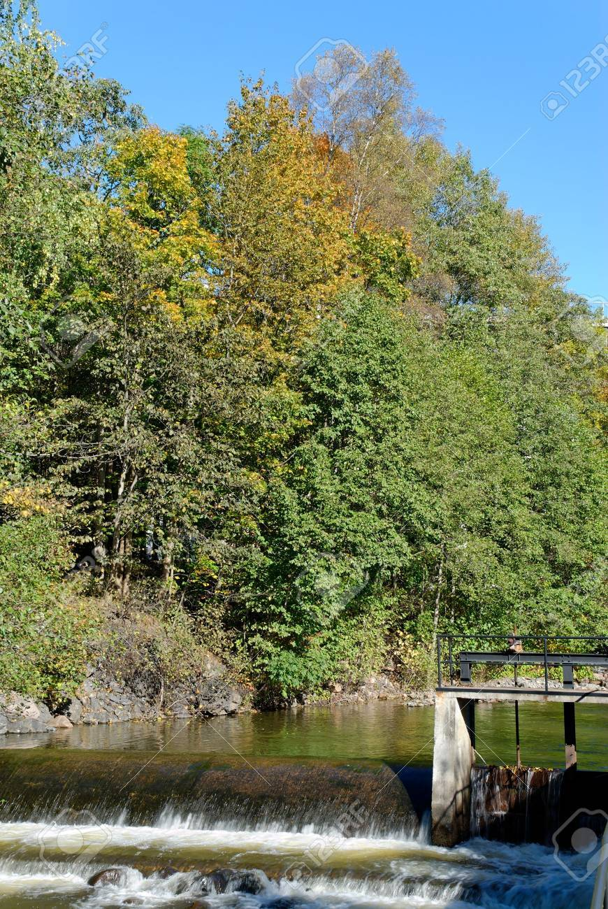 A river calmly flowing over a small dam with trees touched by autumn on its bank. Stock Photo - 3685979