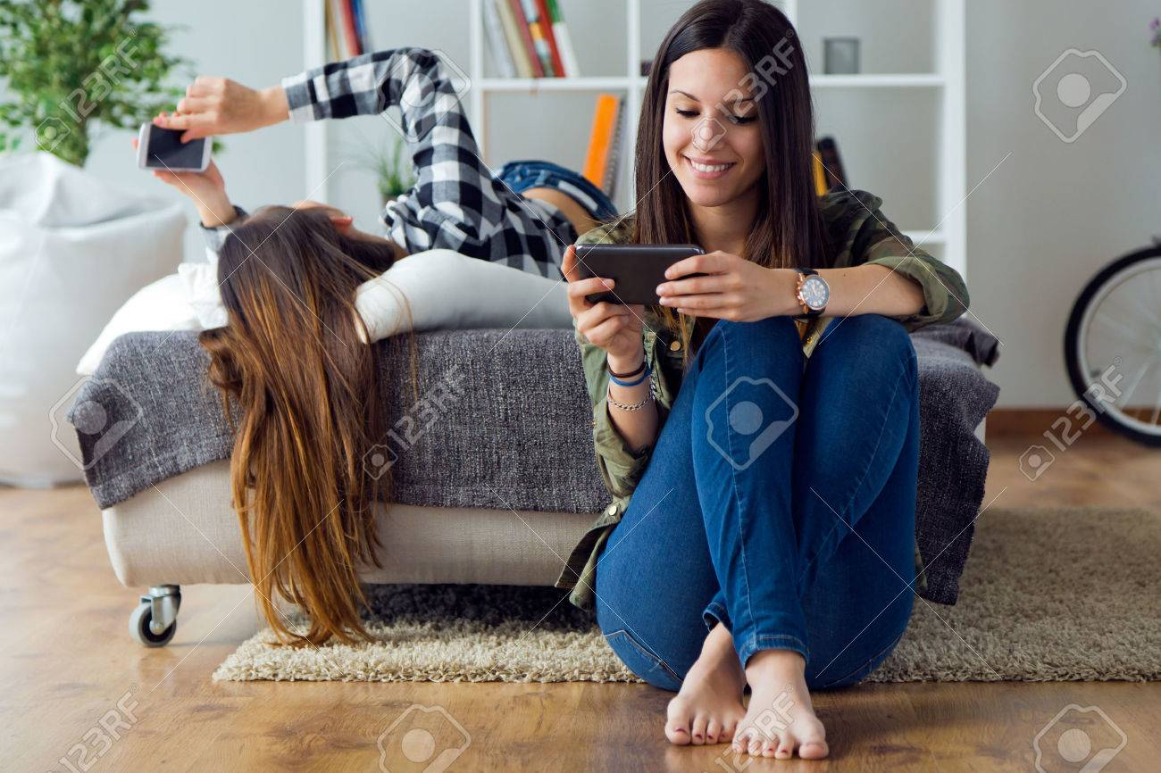 Portrait of two beautiful young woman using mobile phone at home. - 43826395