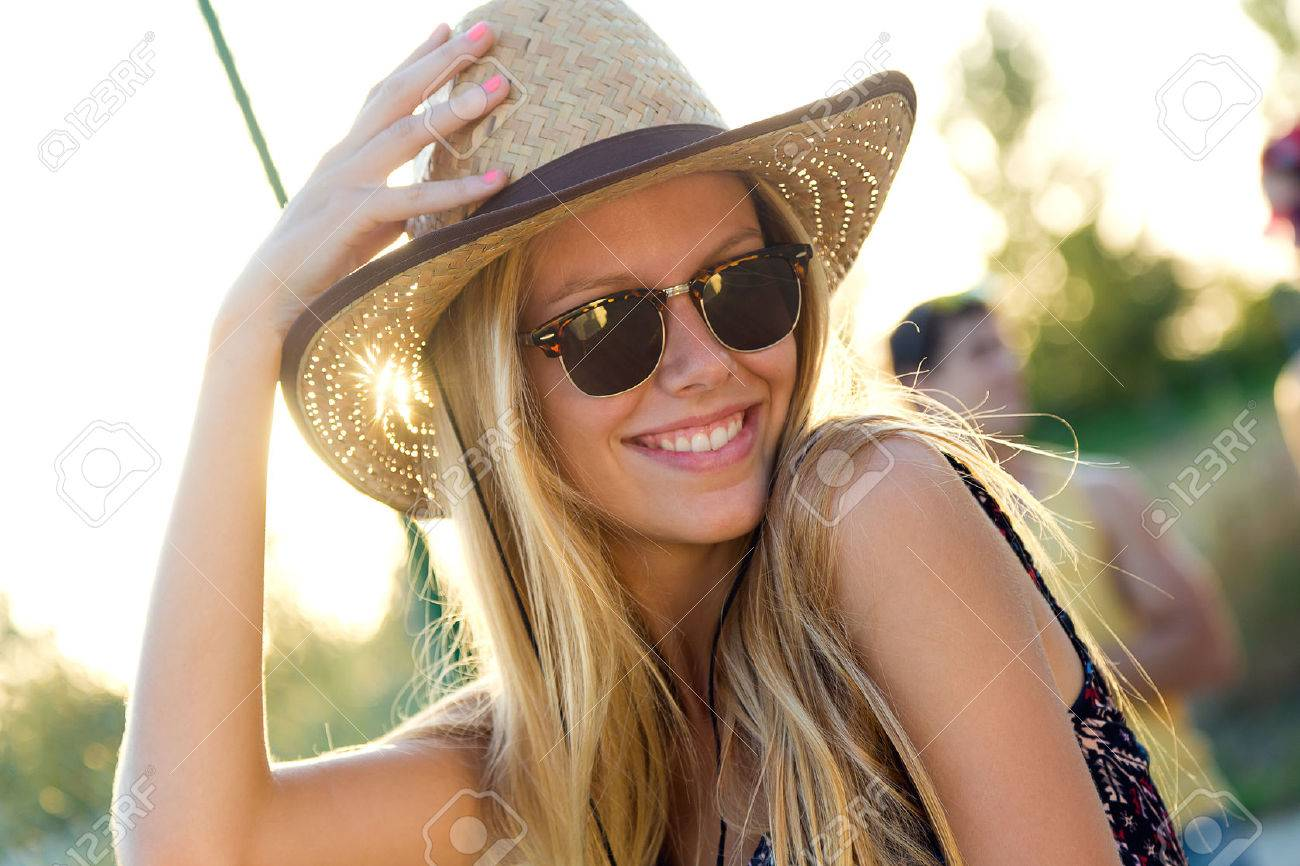 Outdoor portrait of young attractive woman with hat on a summer day. - 43763909