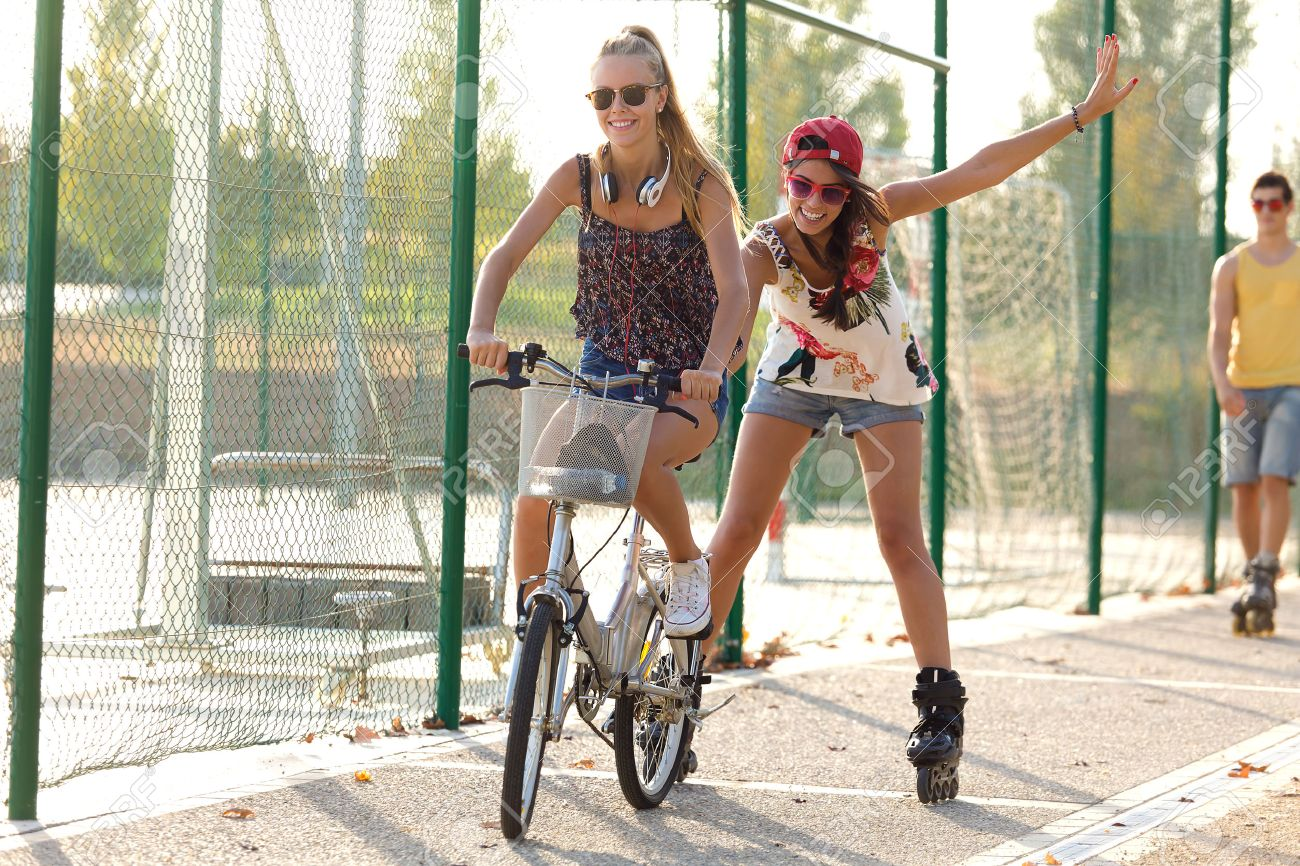 Outdoor portrait of group of friends with roller skates and bike riding in the park. - 43826507
