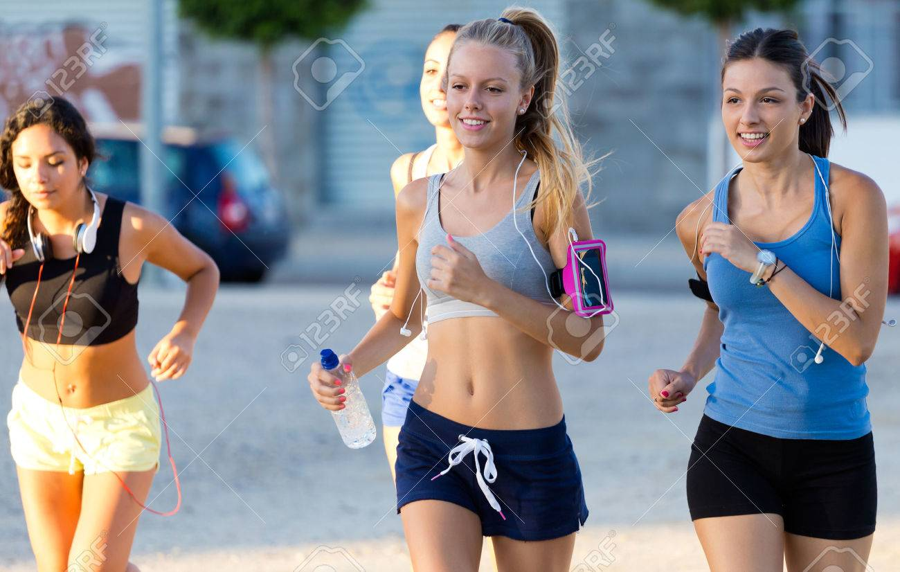 Outdoor portrait of group of women running in the park. - 43826652