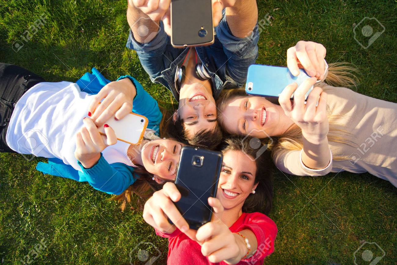 Outdoor portrait of group of friends taking photos with a smartphone in the park - 43826752