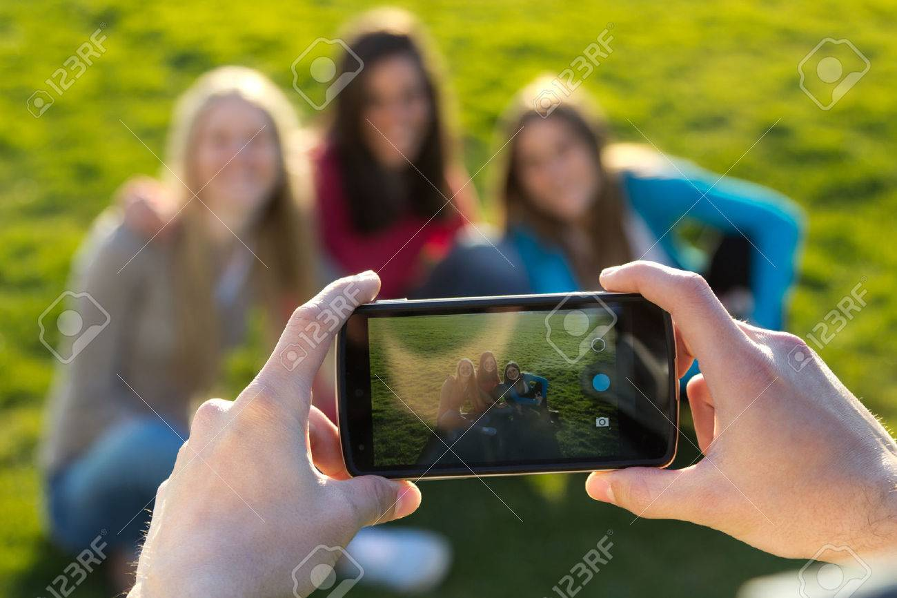 Outdoor portrait of group of friends taking photos with a smartphone in the park - 43826762