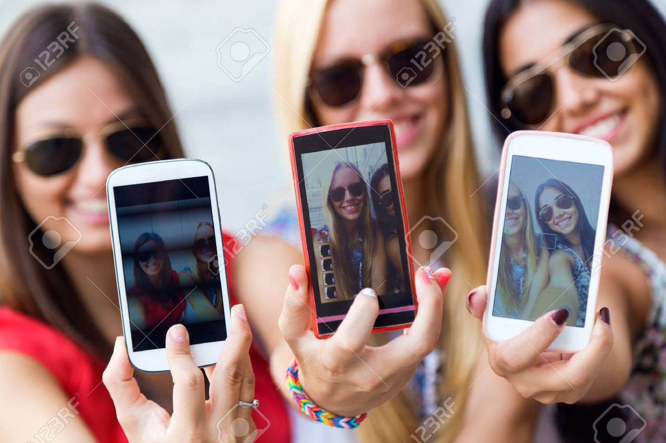 Portrait of three friends taking photos with a smartphone - 43826764