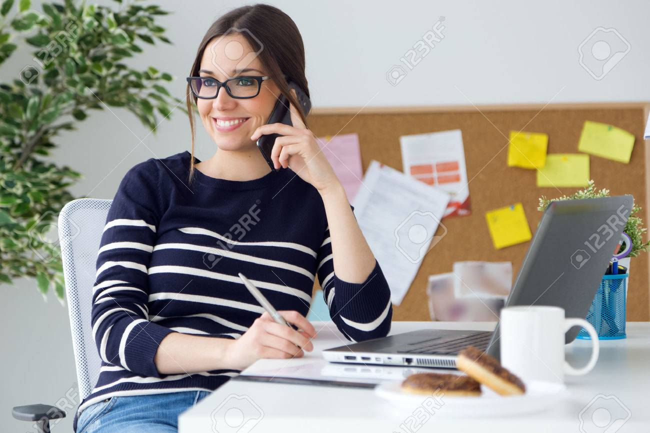 Portrait of confident young woman working in her office with mobile phone. - 44039754