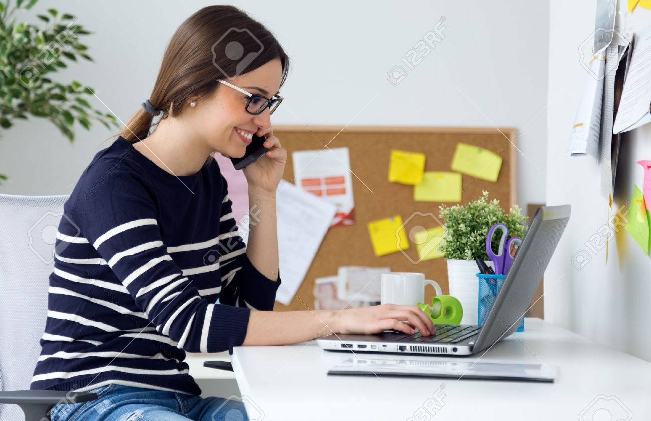Portrait of confident young woman working in her office with laptop. - 43826858