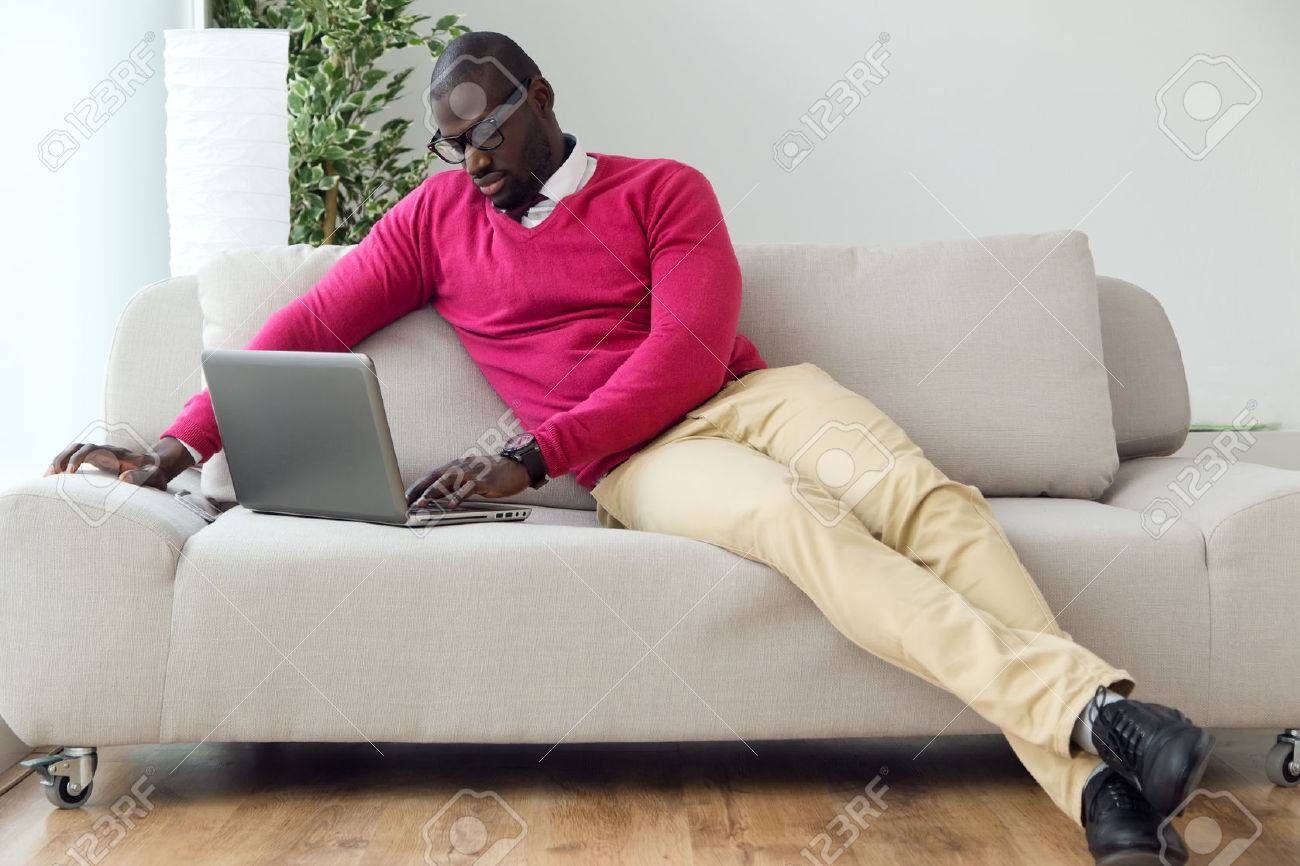 Portrait of handsome young man working with his laptop at home. - 51873503