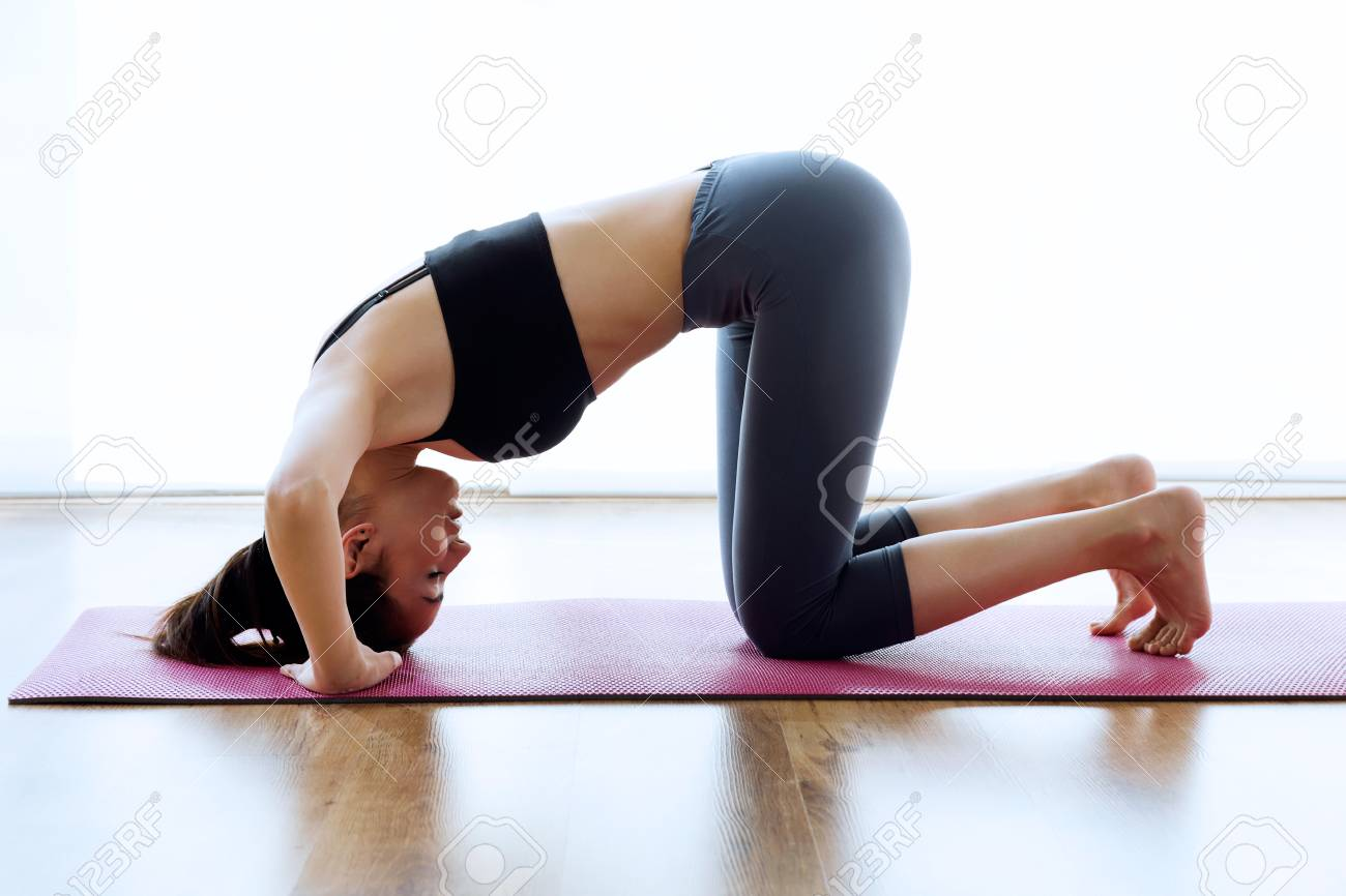 Portrait of sporty young woman doing hypopressive abs indoor. - 98593049