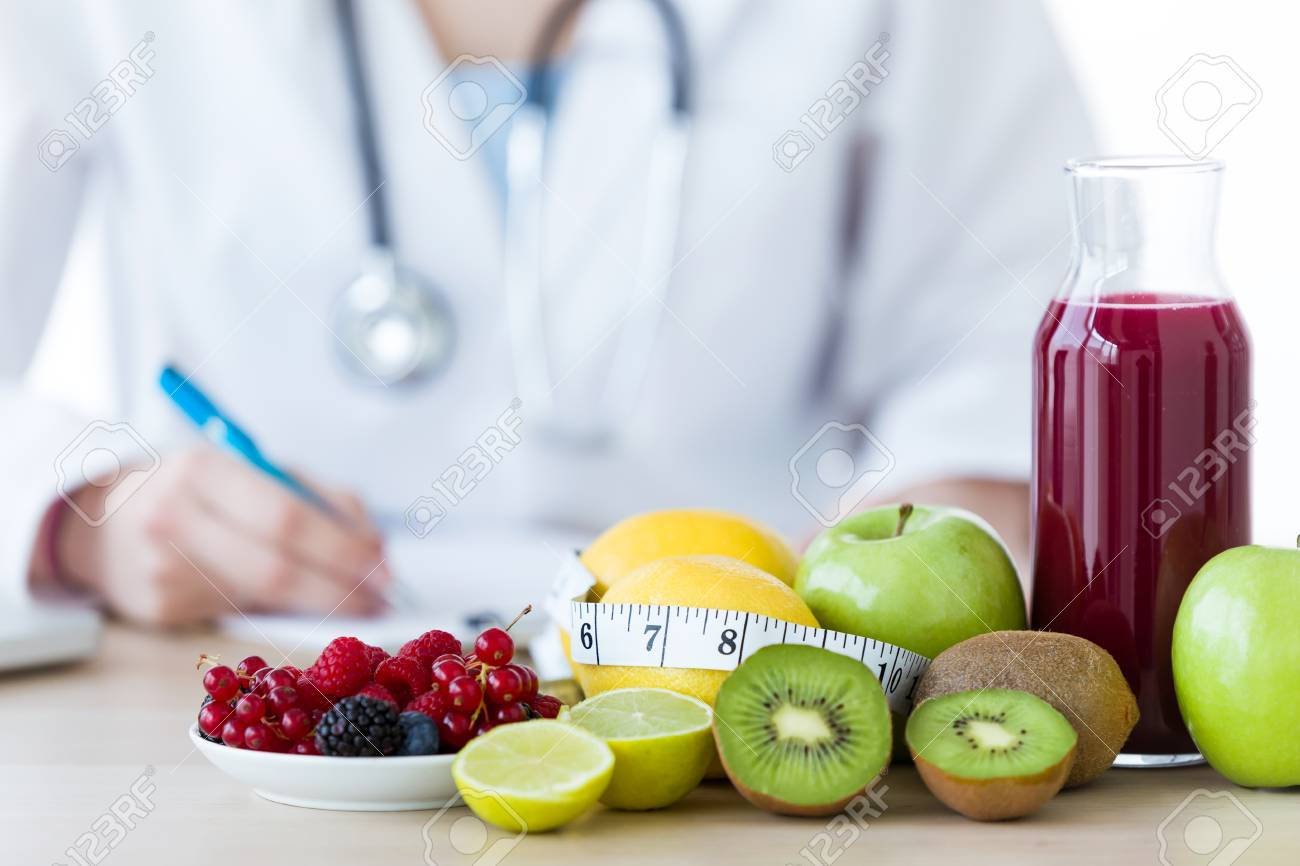 Close-up of some fruits such as apples, kiwis, lemons and berries on nutritionist table. - 98593163