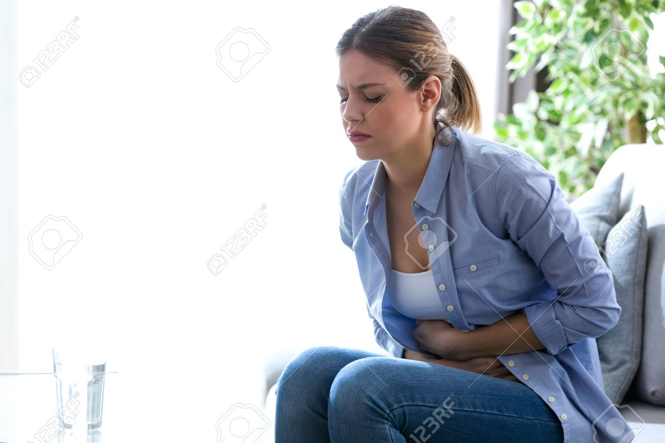Shot of unhealthy young woman with stomachache leaning on the couch at home. - 99373416