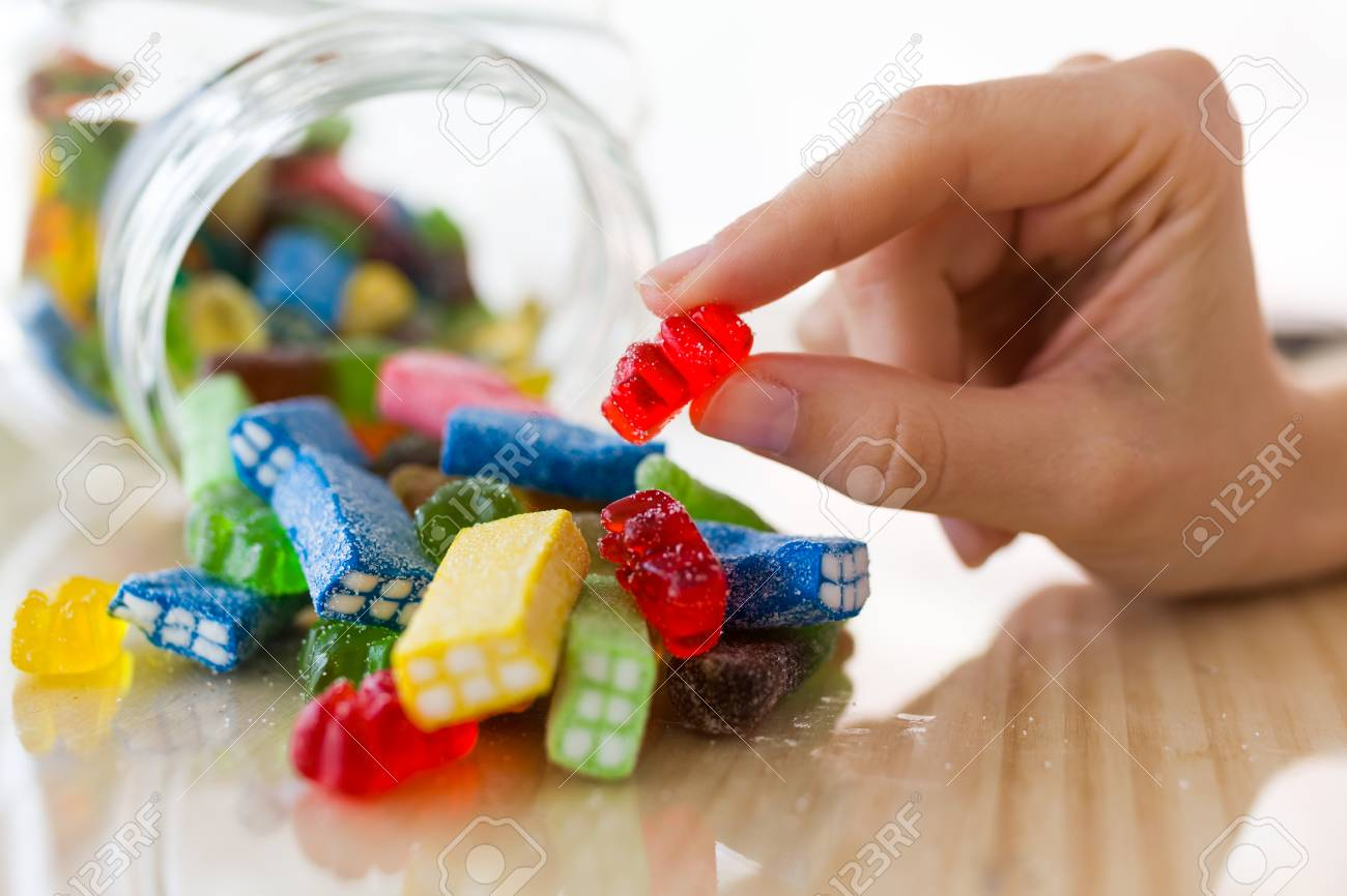 Close-up of the hand of young woman taking colorful jelly candies. - 102005755