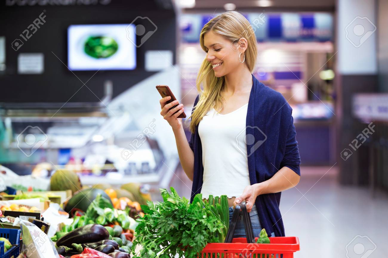 Shot of beautiful young woman looking shopping list on mobile phone while buying fresh vegetables in the market. - 107452048