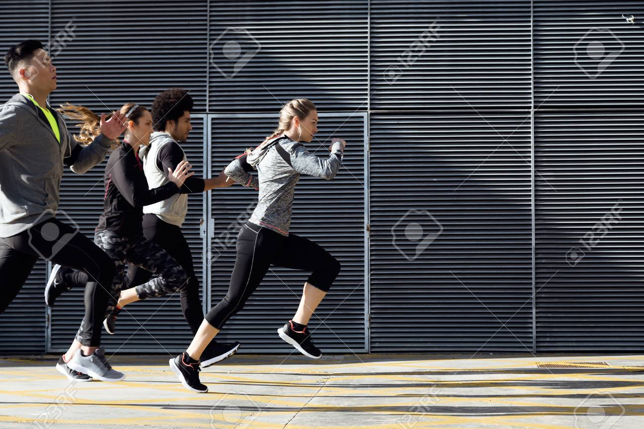 Outdoor portrait of group of friends running in the city. - 111518922