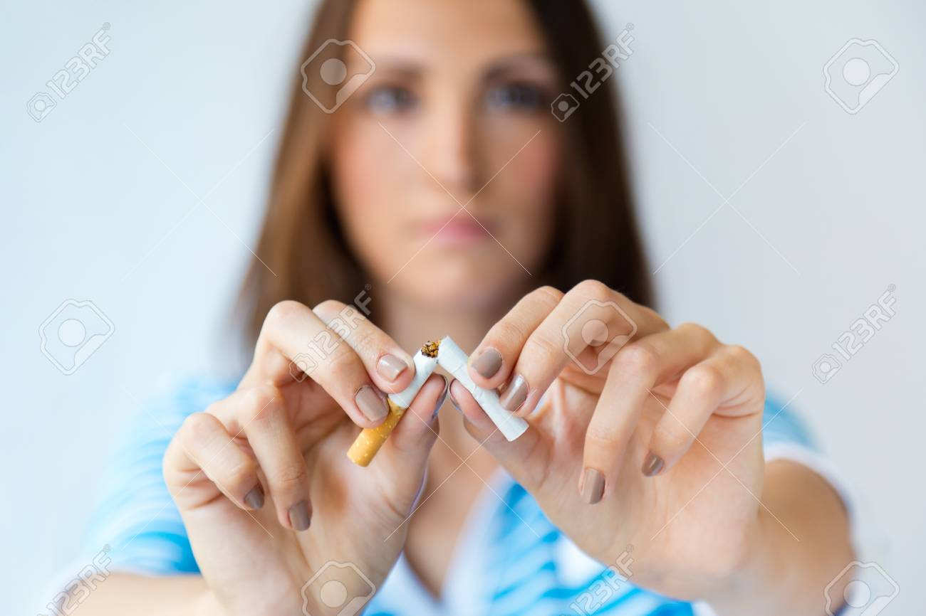 Portrait of young woman refuses to smoke and breaks cigarette. - 111657576