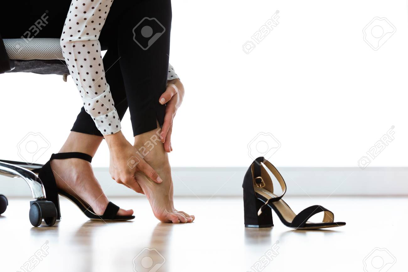 Close up of businesswoman sitting on a chair and massaging her hurting toes after wearing every day heels. - 111525140