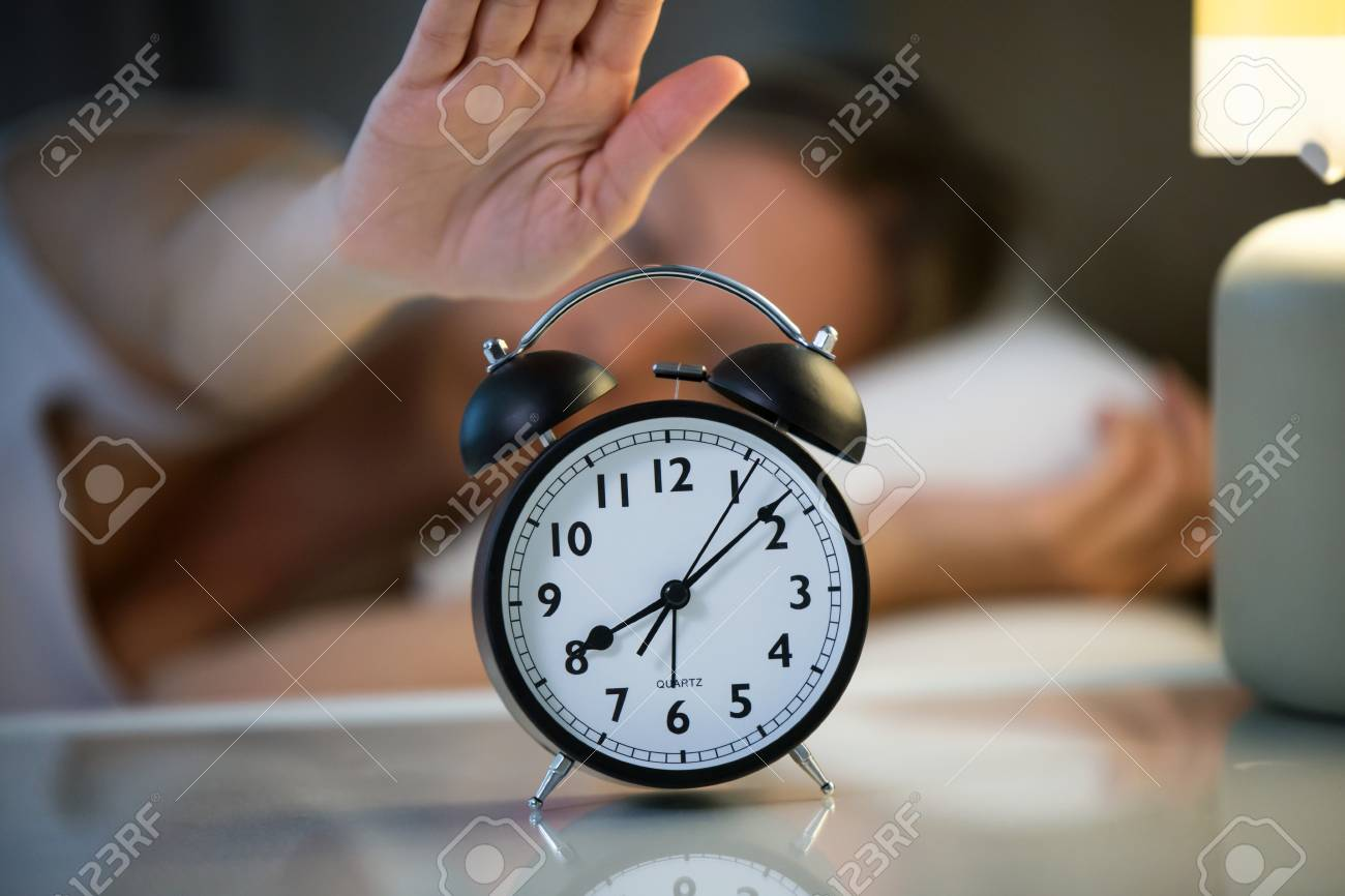 Shot Of Pretty Young Woman Turning Off The Alarm Clock In Bedroom