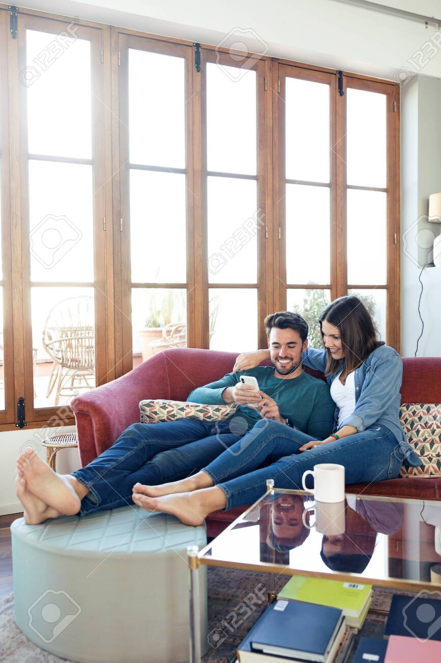 Shot of lovely young couple using they mobile phone while sitting on sofa at home. - 121694231